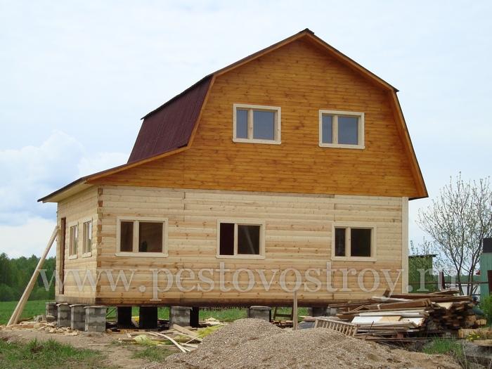 Фотография дома из брусас брусовой верандой и мансардной крышей